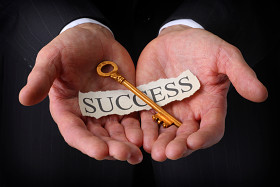 Hands holding a key labeled 'success'
